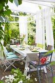 Gedeckter Terrassentisch und farbige Sitzpolster auf Stühlen unter Pergola mit luftigen Vorhängen auf weißem Gestell