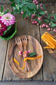 Wooden cutlery on wooden plate decorated with spindle seed pods next to bowl of Savoy cabbage leaves and zinnias