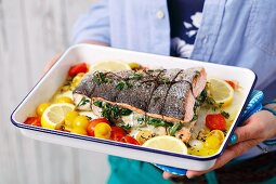 Salmon filled with spinach and prawns in a baking dish with roasted cherry tomatoes