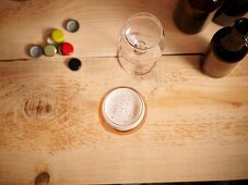Beer glasses, beer bottle caps and beer bottles on a wooden surface