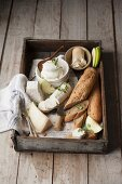Various types of cheese and a baguette on a wooden tray