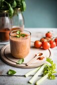 A glass of tomato smoothie with fresh basil leaves and vine tomatoes