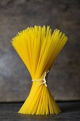 A bundle of spaghetti tied with string standing on a grey surface