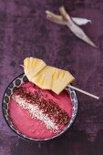 A smoothie bowl with pineapple and beetroot