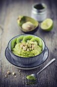A smoothie bowl with fruit purée, avocado, matcha and almond crunch