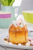 A mini sponge cake with caramel sauce and marshmallows