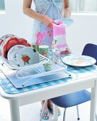 Floral crockery in drying rack on kitchen table; woman holding tea towel and pale blue plate