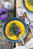 Cream of pumpkin soup with herbs and flowers on a wooden table
