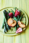 An arrangement of green asparagus and green beans, strawberries and peaches