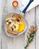 Butter-poached hake with carrot purée and anchovy chips