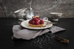 A raspberry and vanilla tartlet topped with grasshoppers