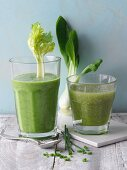 Two green smoothies garnished with celery sticks and bok choy