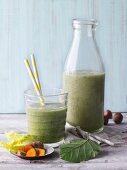Two green smoothies garnished with turmeric and hazelnuts