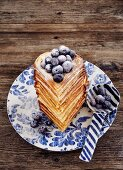 A waffle heart stack with blueberries and icing sugar