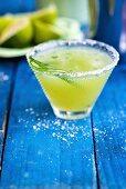 Cucumber margarita in a glass with a salt rim