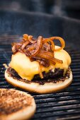 A hamburger with cheese and toasted onions on a grill