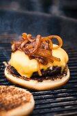 Hamburger mit Käse und Röstzwiebeln auf dem Grillrost