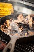 Räucherchips in der Pfanne auf Grillrost