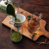 Akelei-Wein nach Hildegard von Bingen zubereiten: Akeleisaft in eine Flasche gießen