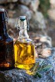 Olivenöl in Flasche auf Steinmauer