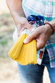 Mann hält eine Packung Spaghetti