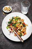 Tomato-infused barley risotto with tofu, peanuts and spinach