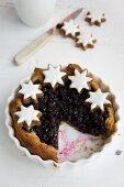 A sliced blueberry shortcrust tart with cinnamon stars