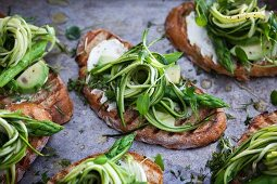 Bruschette with avocado, fresh cheese, purslane, asparagus and zucchini