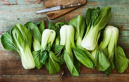 Bok choy with a knife on a wooden board