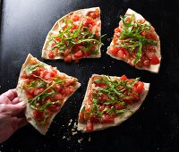 A hand taking a slice of bruschetta pizza