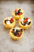 Baked pasta and Parmesan baskets filled with caprese salad