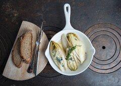 Chicoree mit Roquefort im Ofen überbacken, thailändischer grüner Pfeffer und Holzbrett mit Landbrot