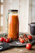 A jar of homemade ketchup with cherry tomatoes
