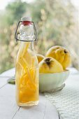 Quince schnapps in a bottle, with fresh quinces in a vintage bowl in the background