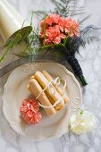 Sponge fingers tied with string and salmon-pink carnations on white plate next to bouquet of carnations on marble surface
