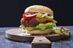A hamburger on a wooden board