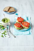 Open sandwiches topped with green pea and avocado cream, cheese, grilled peppers and tomatoes