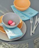 Farbige Schalen auf Stoffservietten mit verschiedenen Tangram-Motiven