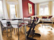 Esstisch mit Glasplatt und mit schwarzem Tripp Trapp Stuhl, im Hintergrund gemütliche Eckcouch vor Fenster, seitlich bordeauxrot getönte Wand