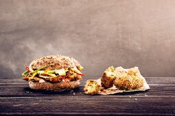 A seeded roll with cajun chicken breast and falafel, avocado, apple and mayonnaise