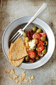Tomato salad with dried and fresh tomatoes, olives and crispy unleavened bread