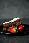 A slice of chocolate cake with icing sugar and strawberries