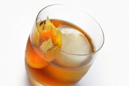 Barrels Shot drink with an ice cube and physalis (close-up)
