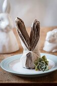 A dinner place set with a folded bunny napkin and a succulent plant