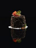 Black food: black rice timbale with bacon, foam and a leaf on a black reflective surface