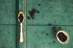 Getrocknete Cranberries in einem Löffel und Schälchen auf rustikalem Untergrund