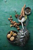 Verschiedene Weihnachtsgewürze und Nüsse in Backförmchen auf rustikalem Holzuntergrund