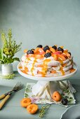 Apricot pavlova with apricot sauce and blackberries on a white cake stand