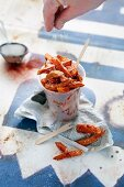 Sweet potato chips in a plastic cup being sprinkled with salt