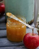 Apple, ginger and lemon jam in a glass jar with a knife